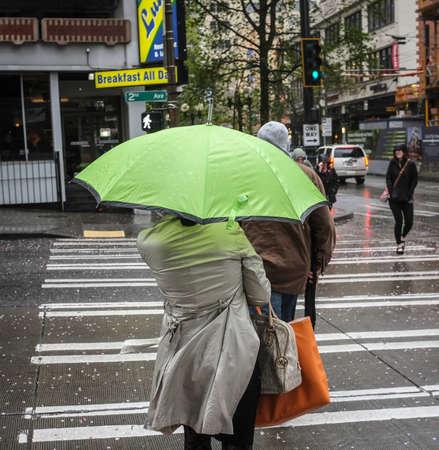strom: A green umbrella crossing a street in a storm.