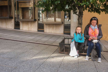 mother on bench: Mother and daughter waiting on a street bench. Editorial