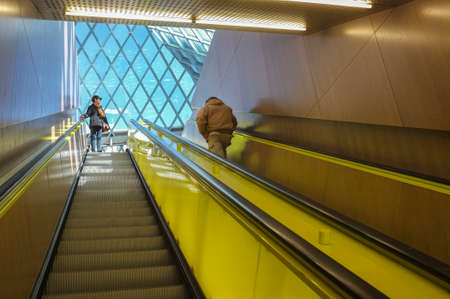 Two people riding an art museum escalator. Editorial