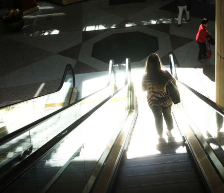 Woman on an escalator, strongly lighted. Editorial