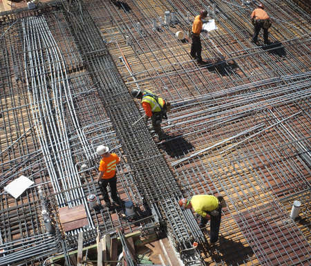 on rebar: Construction workers laying re-bar.