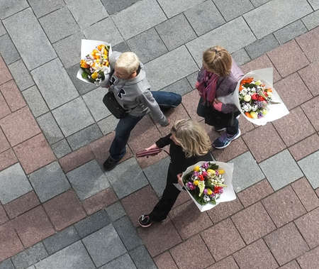 overhead view: Overhead view of three woman carrying large bouquets of flowers.