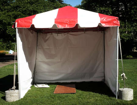 An empty red and white pavilion style small tent.