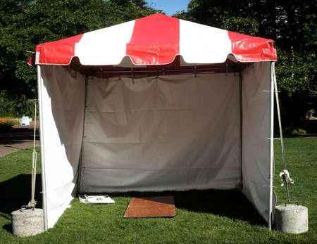 A red and white tent, pavilion, empty.