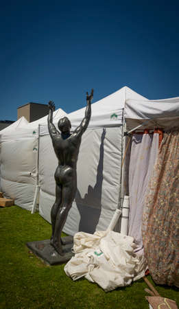 Nude statue reaching for the sky over tents