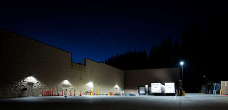 A large lighted loading dock area at night with trailers, at night.