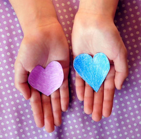 Teenage hands holding two hearts
