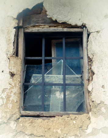 Old window on ruined wall