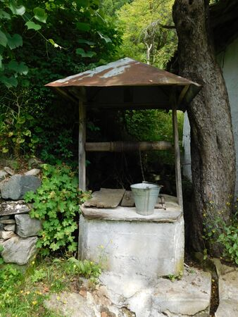 A picture of an old well that is in a very old village Stock fotó