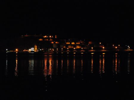 A breathtaking view of a summer night with street and house lights on a small island.