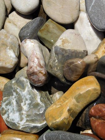 A pile of beautiful and colourful rocks and pebbles that are from the ocean.