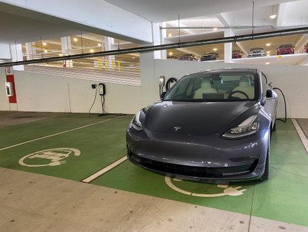Orlando, FL/USA-4/10/20: A gray Tesla Model 3 charging at a free garage charging station.