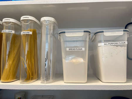 An organized pantry shelf with various types of pasta and flour in plastic containers. Foto de archivo