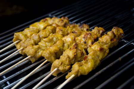 Bite-sized chicken pieces on a skewer, malaysian style -- called satay.