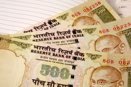 three 500 rupee indian currency notes on a ruled paper notebook photo