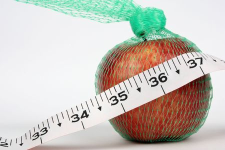 inch: An apple in net with 36 inch in focus reflecting perfect health Stock Photo