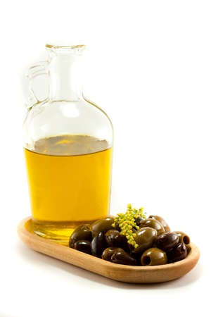 Glass bottle of olive oil next to mixed olives on a wooden plate