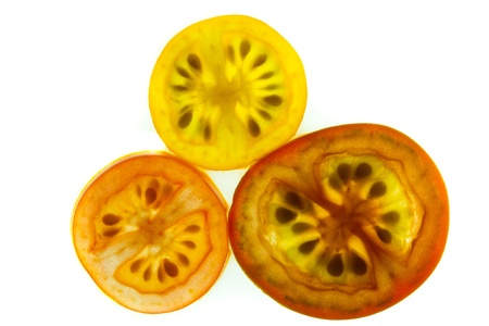 Red, yellow, and orange grape tomato slices on a white background
