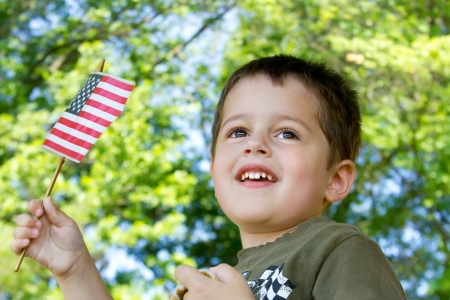 Portrait of a cute brown-haired, brown-eyed boy waving an American flag as he watches a parade Reklamní fotografie