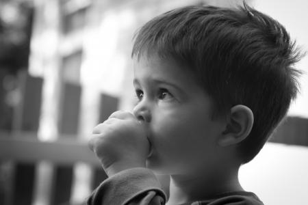 그의 엄지 손가락을 빠는 귀여운 어린 소년의 흑백 측면보기 초상화