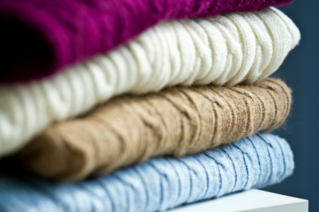 Stack of folded cable knit sweaters
