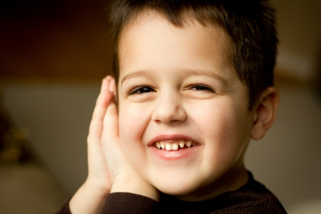 Close-up portrait of a cute little boy with brown hair and brown eyes smiling with his hands pressed to the side of his face.