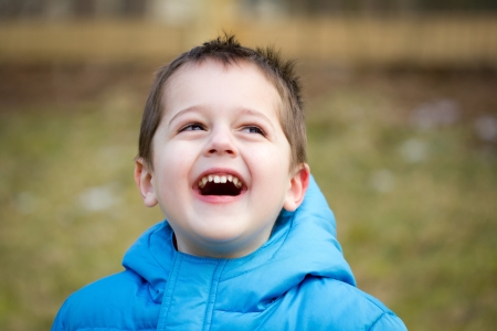 Portrait of a cute little brown-haired boy with a happy, joyful expression on his face.  He is wearing a blue coat and is playing outside. Reklamní fotografie