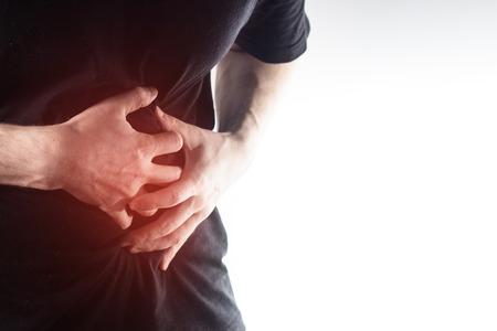 hombre, individuo en un negro camiseta sobre un fondo blanco se dan la mano sobre su estómago, dolor de hígado, el páncreas, los riñones