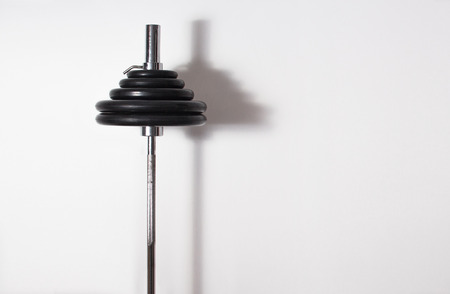sport barbell standing against a white wall in gym, flat, trend, 2017, sporty lifestyle, spase