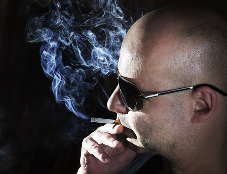 lighting background: middle aged man smoke cigarette at the black