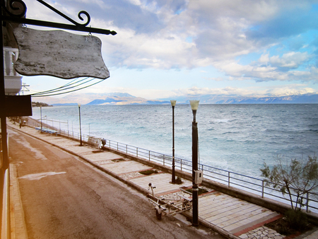 Wooden signboard on the street, layout, against the background of mountains, the sea in the