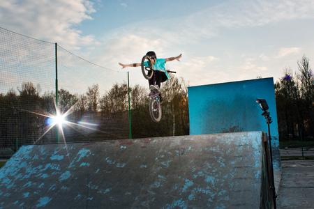 Extreme biker makes a dangerous stunt in the summer bmx park Stock Photo