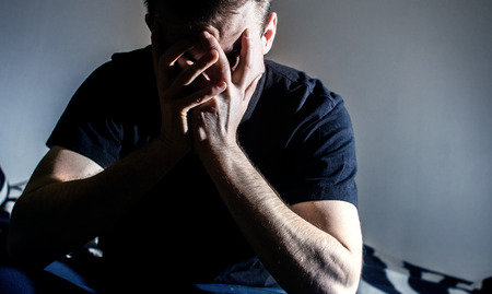 Low-key  portrait of stressed young  man with hands on a face, lonely, sad,  negative emotions Stock Photo