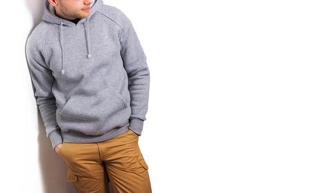 de man in de lege grijze hoodie, sweatshirt, staan, glimlachend op een witte achtergrond, mock-up, vrije ruimte, logo, sjabloon voor afdrukken, ontwerp