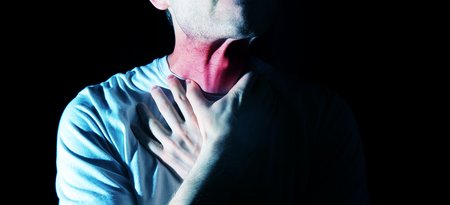 The man touches his sore  throat, neck, Temperature, runny nose, illness Stock Photo