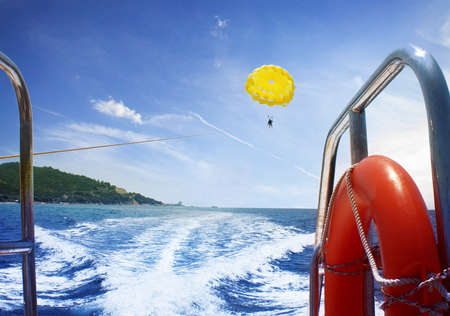 Man is flying on a paraglider on the sea from a boat