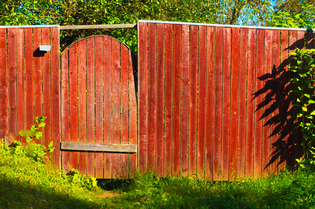 wicket gates on a red wooden fence in the village