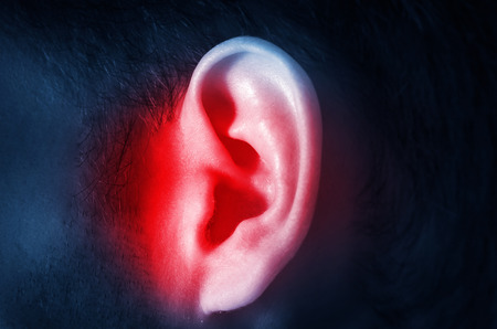 human male ear on a dark background isolated