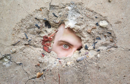 peephole: male eye looks through a hole in the concrete wall, looking for information, spy