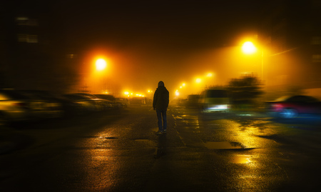 a mysterious man stands alone in the street, among cars in an empty city, walks the night street, dreams