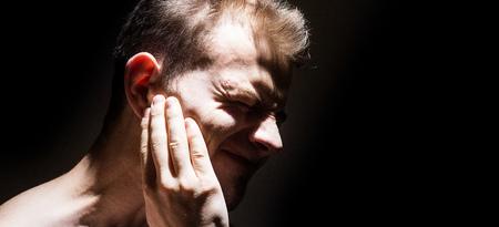 귀울음, 고통에서 고통 아픈 귀를 들고 검은 배경에 고립 된 사람 스톡 콘텐츠