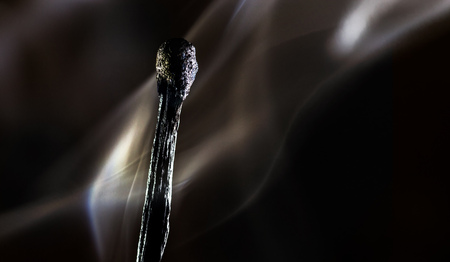 Burned match on a dark background with smoke