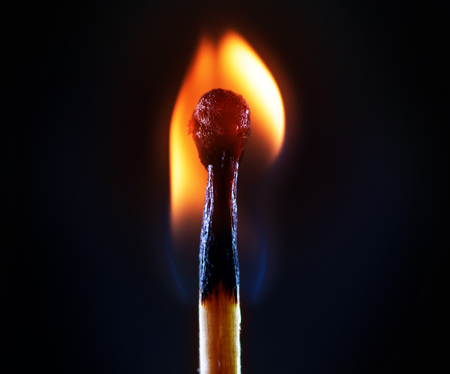 burning match against a dark background