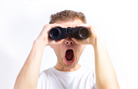 man with binoculars in hands on a white background isolated looking at the camera