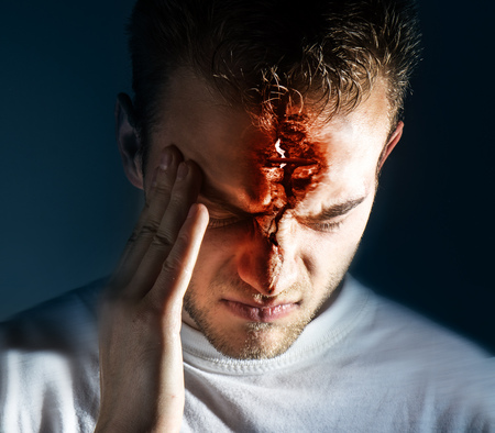 man hold his had and suffering from headache, pain, migraine, sad depressed on black background, in a white t shirt
