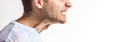 man with clenched teeth on white background, angry grin, toothache on white background Фото со стока