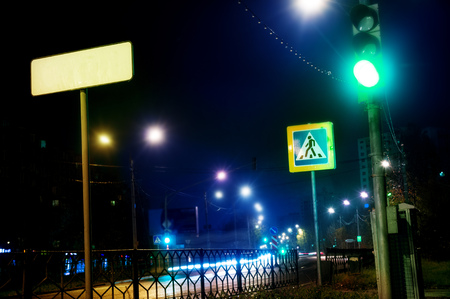 green traffic light at night, pedestrian crossing in the city on the street