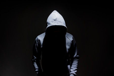 Silhouette d'homme dans la cagoule, homme mystérieux sombre à capuche, meurtrier, pirate informatique, anonymus sur fond noir avec espace