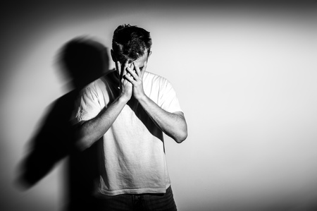 sad man with hands on face in sadness, on white background, black and white photo, free space