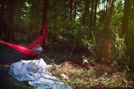 man lies in a hammock in the forest, tourist traveler's rest
